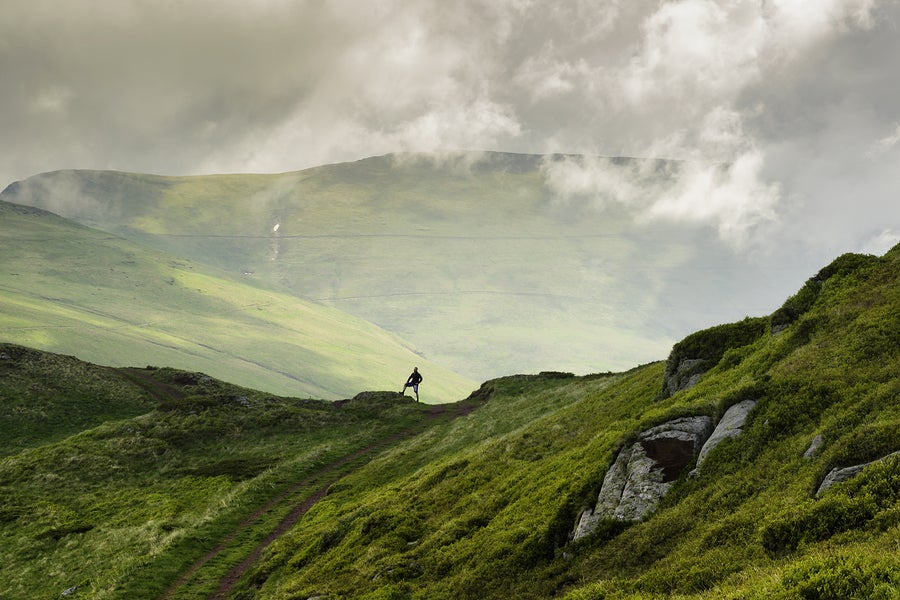 landscape shot of a hiker on a mountain ridge.